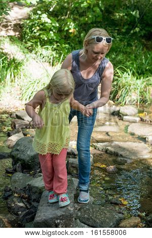 Mum And Daughter Carefully Cross River On Stepping Stones