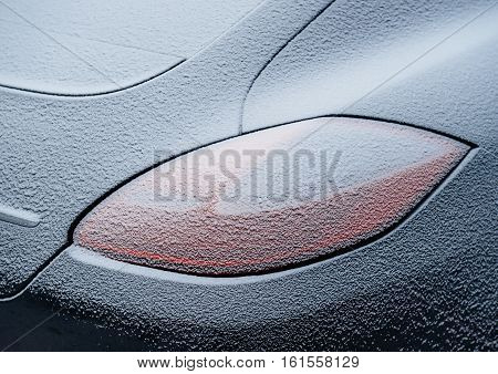 rear light of a luxury car covered with snow