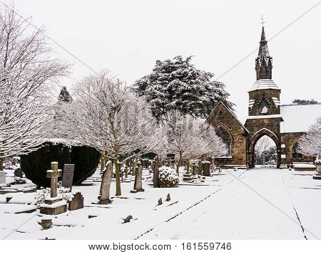 Peaceful snowy winter scene at the local town cemetery in Melbourne, Derbyshire, England
