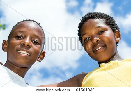 Close up low angle face shot of two african kids together against blue sky wit clouds.
