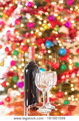 Empty drinking glasses vintage cork screw and unopen wine bottle on Mahoney table with bright Christmas tree lights in background. Vertical format layout.