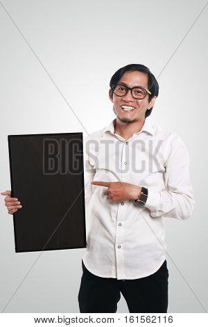 Photo image portrait of funny Asian businessman or teacher or student showing empty blackboard with smiling face holding blackboard with one hand while other hand pointing to it