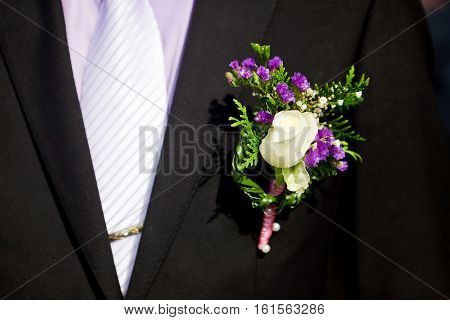 boutonniere of white roses on a black men's suit. selective focus