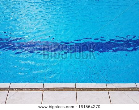 Refreshing view of edge of swimming pool with blue background of sparkling crystal clear water with reflection on sunny day
