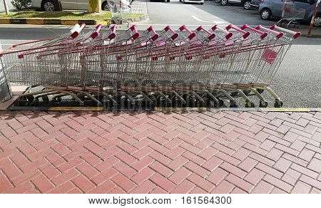 Line- up of empty shopping trolleys/ carts in a row stacked outside of shopping area by the side of the pavement.