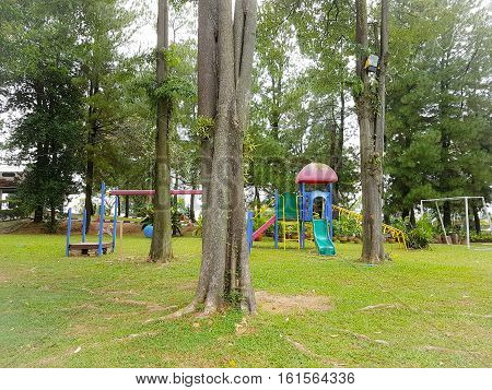 Colorful children's playground with trees and grass in sight in a peaceful and serene environment for recreation activities.