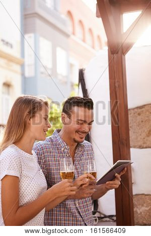 Happy Couple With Beers Using Tablet