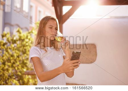Girl Looking At Cellphone Sipping Beer