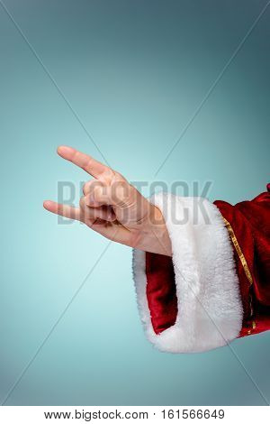 Photo of Santa Claus hand in rocker gesture on blue