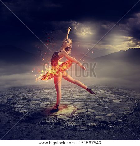 Young blond ballet dancer dancing on fire