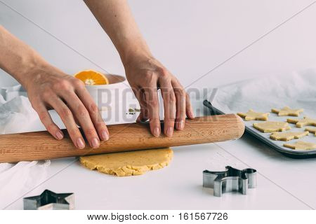 Woman Rolling out Biscuit Dough on White Table to Make Christmas Biscuits