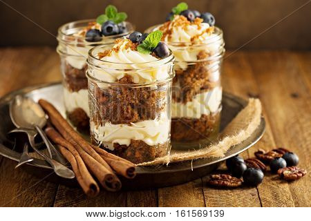 Carrot cake in a jar with pecan nuts, blueberry and cream cheese frosting