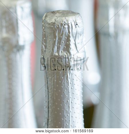 Silver champagne bottle necks and top caps at standing the light background in liquor store
