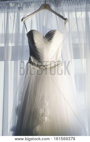 Wedding Dress On The Hanger Before The Window
