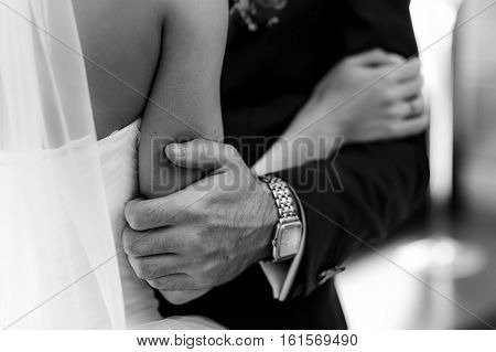 Amazing fiance's hand holds bride's elbow in the room