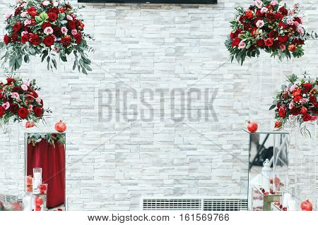 Rich Red Bouquets And Pomagranates Stand In The Front Of White Brick Wall
