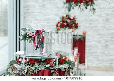 Glass Box On Round Table Covered With Red  Cloth, Roses And Greenery