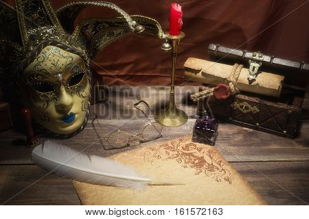 Theater concept. Vintage still life with quill and scroll near mask, old chest, glasses and candle in candlestick on red background.