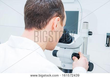 Young male medical researcher looking through microscop slide in the life science (forensics microbiology biochemistry genetics oncology) laboratory. Medicine concept.