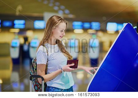 Beautiful Young Tourist Girl In International Airport Doing Self Check-in