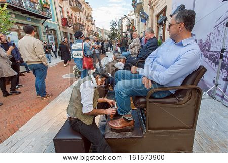 TBILISI, GEORGIA - SEP 25, 2016: Elderly shoe cleaner rubs the client shoes on the street during a outdoor festival on September 25, 2016. Tbilisi has population of 1.5 million people