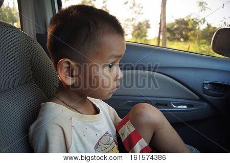 Sad boy sit down in the car