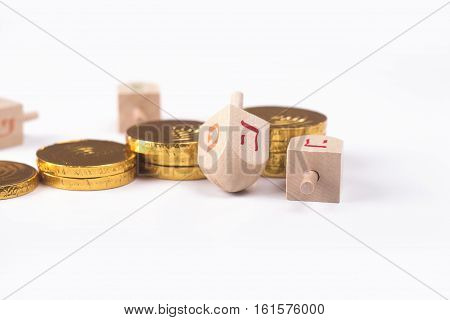 Image of Jewish holiday Hanukkah with chocolate coins and wooden dreidels (spinning top)