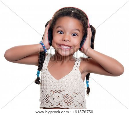 Funny african american small girl listening to music on wireless headphones isolated on white