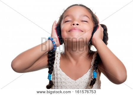 Cute african american small girl listening to music on wireless headphones isolated on white
