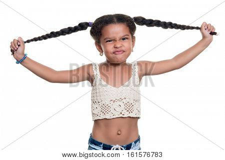 Cute african american small girl with a funny angry face pulling her hair isolated on a white background