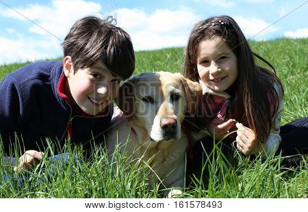 young child and little girl with yellow Labrador Retriever dog