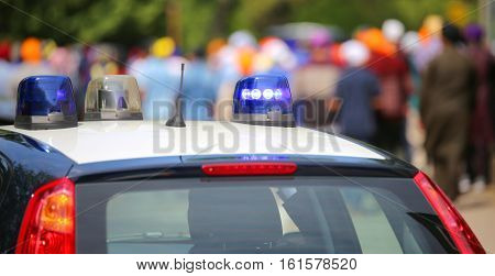 police car with blue sirens during the riot with a lot of people