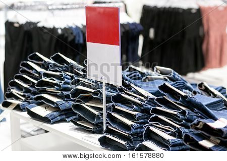 Stack of jeans with sale label on show-window.