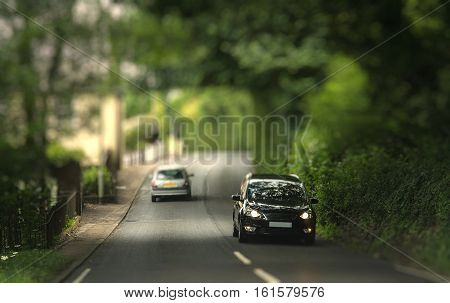 Cars traveling in the tunnel of trees. Typical Devonian road. Miniature Effect.
