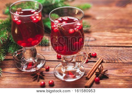 Glass of mulled wine with cranberry and scented cinnamon sticks on a wooden table