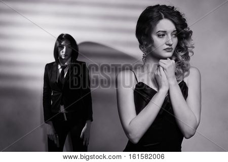 Woman In A Long Black Dress And A Girl In A Black Suit