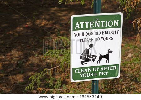 Close up of a weathered sign urging dog owners to clean up after their pets