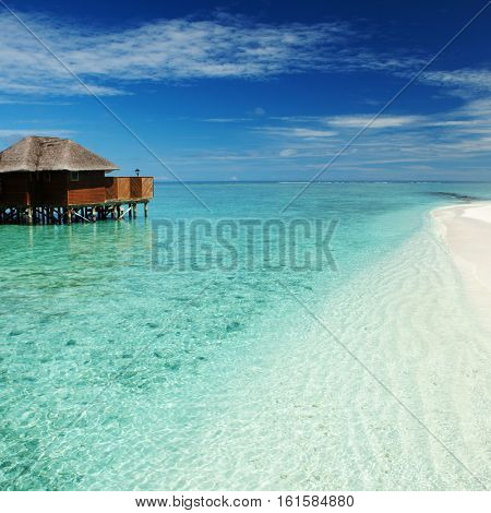 Tropical beach. Ocean waves and cloudy sky background. White sand and crystal-blue sea. Ocean water nature, beach relax. Summer sea vacation. Maldives islands sea background