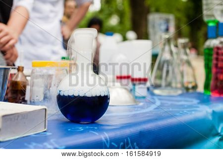 Various chemical utensils on the table. In front is a flask in which a chemical reaction