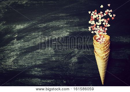 Ice Cream Horn with Sweethearts on a Chalkboard. Love Valentine's Day or Creative Concept. Top view