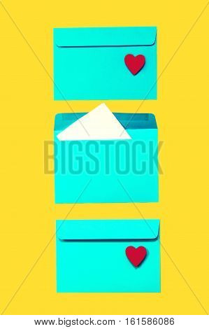 Beautiful Colorful Blue Envelops with Red Hearts on Yellow Background Fashion Style Flat Lay Top View. Message Love Message or Love Concept.