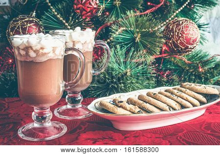 Christmas still life - two cups of winter hot drink cacao with marshmallows and chocolate cookies. Spicy hot chocolate on background of Christmas tree. Happy New Year. Moody style. Selective focus.
