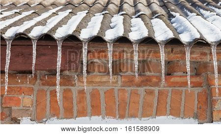Icicles on the roof of the house in front of brick wall winter background