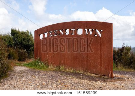 Large sign in rusty metal on the highway entering the mining town of Queenstown on the west coast of Tasmania