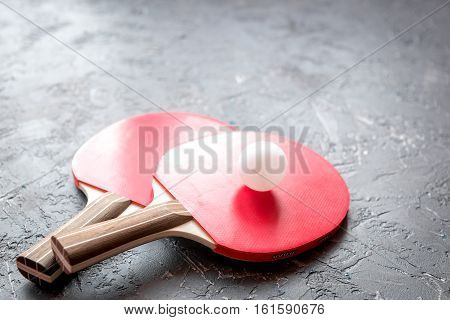 red racket for ping pong ball on gray background close up