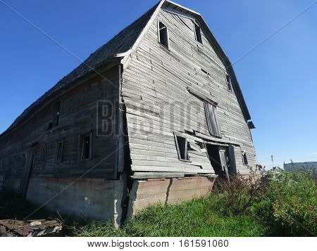 A abandoned barn on a farmstead with a crumbling foundation.