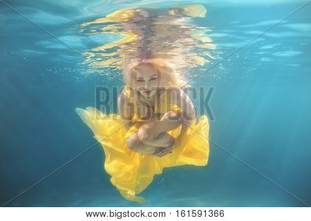 In the pool underwater swim woman she in a yellow dress.
