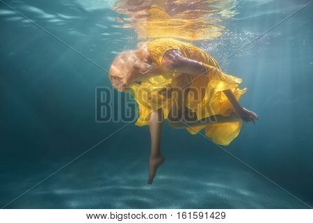 Woman underwater shows figures she is dressed in a yellow dress.