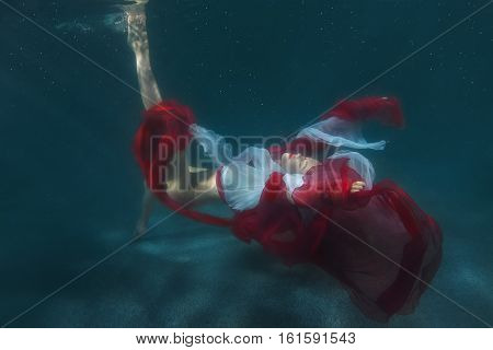 Dancing woman underwater she is wearing a red dress.