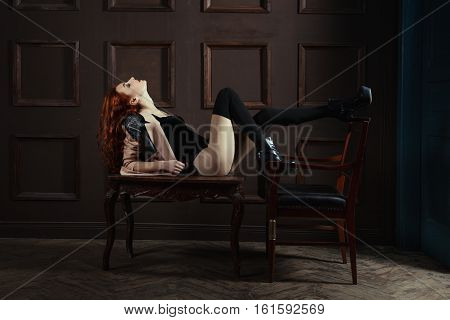 Red-haired woman lying on the coffee table she playfully flirts.